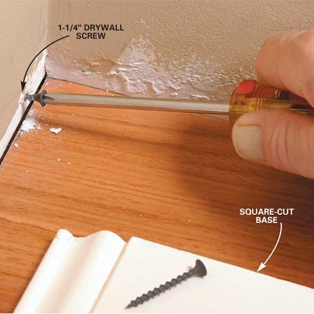 <b>Photo 2: Fix a gap at the bottom</b><br/>Close a gap at the bottom by removing the square-cut base and driving a drywall screw into the wall about 1/2 in. from the floor. Test the cope and adjust the screw in or out until the cope fits tight.