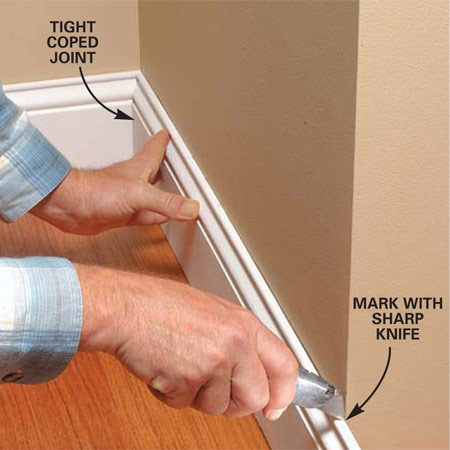 <b>Photo 1: Use a knife to mark outside corners</b><br/>Mark outside corners with a sharp utility knife. Repeat the marking process on the opposite baseboard. Cut 45-1/2 degree angles on both boards, leaving each an extra 1/8 in. long.