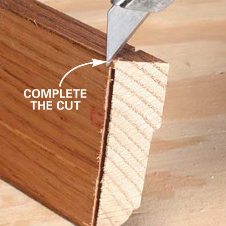 <b>Photo 1: Complete the cut with knife</b><br/>Cut the angle for a small mitered return on your miter saw, but don&#39;t completely cut if off from the trim stock. Rather, cut through the remaining sliver of wood with a utility knife.