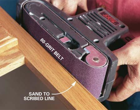 <b>Photo 2: Sanding to the line</b></br> Sand to the line with a belt sander. Bevel the wood slightly for a tighter fit by tilting the belt sander as you sand. Remove more wood from the side that's not visible.