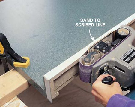 <b>Photo 4: Sanding to the line</b></br> Sand to the line with a belt sander fitted with 100-grit sandpaper. Test the countertop's fit and repeat the process shown in Photo 3 to scribe a new line if necessary. Keep scribing and sanding until you get a perfect fit.