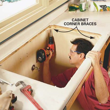 <b>Photo 2: Take out the old countertops</b></br> Unscrew the old countertops or pry them up with a flat bar if they're glued. You'll have to climb into the cabinets to access the screws at the corners.