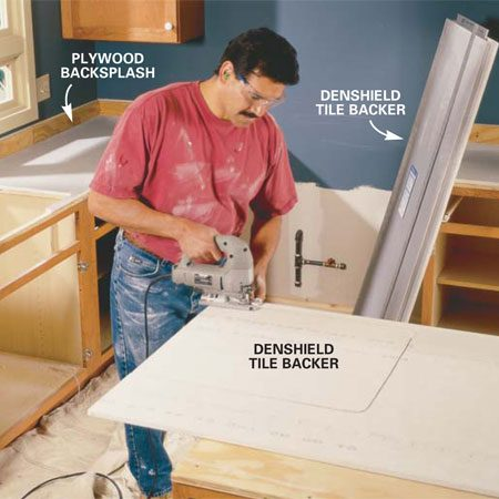 <b>Photo 6:  Cut the tile backer</b></br> Rip 3-1/2 in. wide 3/4-in. plywood backsplash strips and  screw them to the wall with two 2-in. drywall screws into each stud. Score and  snap the tile backer to fit flush with the plywood edges. Span over sink  openings and mark the underside with a pencil, then flip it over and cut out  the opening with a jigsaw.