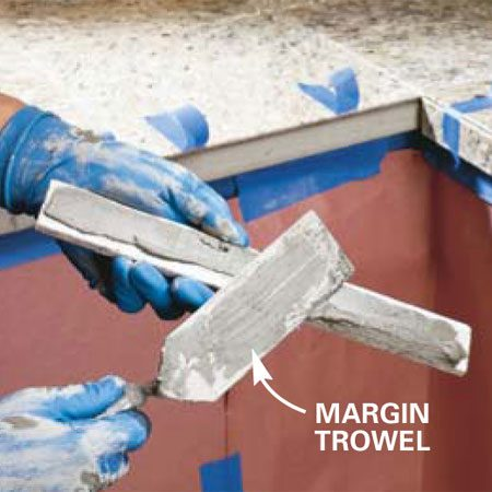 <b>Photo 15: Set the nosing tiles</b></br> Butter the back of the nosing tiles with thinset using a margin trowel and embed them directly below each front tile, leaving a 1/8-in. grout line between the miters. Hold them in place with a couple of strips of masking tape and let them set.