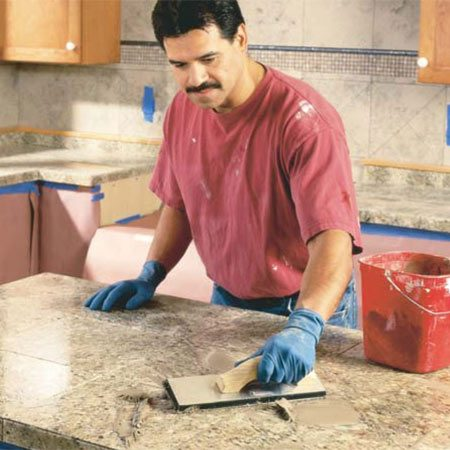 <b>Photo 17: Grout the stone</b></br> Mix unsanded grout to the consistency of peanut butter and work it into the  grout lines with a grout float. Use diagonal swipes across the gaps for good  penetration. Sponge off the excess grout with a damp sponge, rinsing it  frequently in clean water. After the grout dries overnight, buff off the haze  with a clean cotton cloth.