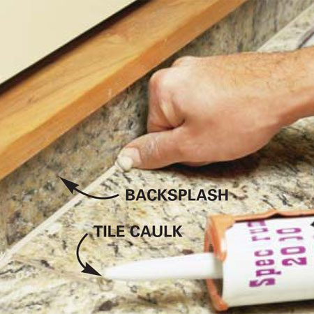 <b>Photo 18: Caulk the inside corners</b></br> Lay a thin bead of colored tile caulk into all inside corners of the  backsplash. Drag the back of your thumbnail through the wet bead to tool the  caulk, then wipe over the caulk with a damp sponge or rag to smooth it out.