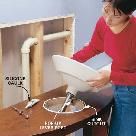 <b>Photo 5: Set the sink</b></br> Squeeze a pencil-width bead of silicone caulk (caulk is usually provided by the sink manufacturer) around the sink cutout and lower the sink into the hole. If your drain has a fancy pop-up lever like ours, face it to the front.