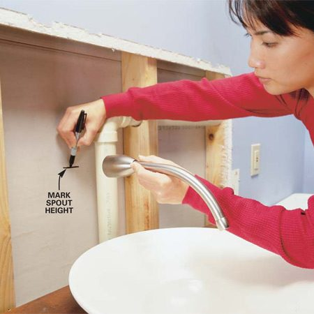 <b>Photo 7: Mark the faucet spout height</b></br> Hold the faucet spout above the sink and mark its center on the wall. Ask your plumbing inspector for the minimum height above the rim. Here, the spout outlet is about 3 in. above the rim of the vessel.
