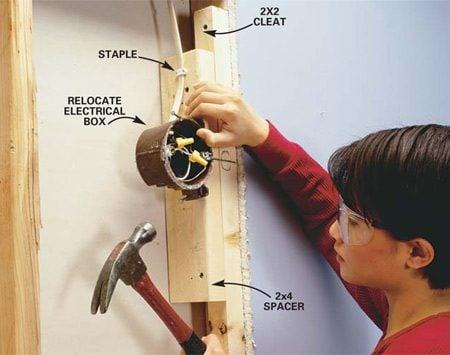 <b>Photo 14: Relocate light fixtures</b></br> Relocate the light fixture boxes if necessary. Turn off the power at the main circuit box and test the wires to be sure it's off. Carefully pry the boxes loose and remove the staples that hold the cables in place. Add blocking or slide the box on its strap to relocate it. Reattach the boxes and staple the cables within 8 in. of the box.