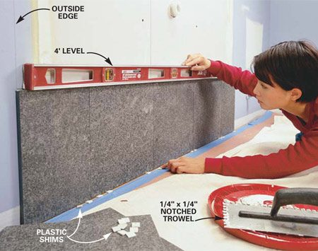 <b>Photo 15: Level the first tile row</b></br> Level the first course of tile with small plastic shims, available at tile retailers. Mark a line with a 4-ft. level to indicate the top of the first row of tile. Draw vertical plumb lines at the outside edges. We extended the tile 1 in. beyond the table on each side.
