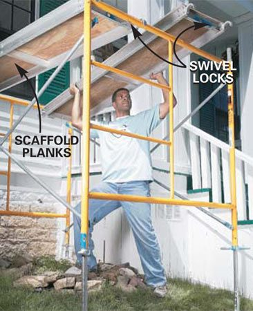 <b>Photo 5: Hook on the planks</b></br> Lift the rented scaffold planks from the middle and angle them up through the frames until both ends are above the frame. Then lower the plank until the ends hook over the frames. Secure the plank with the swivel catches.