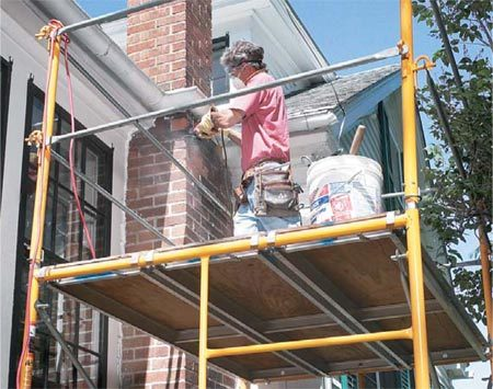 <b>Photo 7: Set up a workstation</b></br> Speed up your work by setting up a workstation on your scaffolding. Pull materials and tools up with a bucket and rope. Major repairs like tuckpointing a chimney are much easier from a scaffold than a ladder.