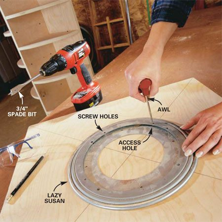<b>Photo 4: Screw the lazy Susan to the base</b></br> Center the 12-in. lazy Susan on the base. Align the screw holes on the top and bottom rings. Locate the access hole in the lazy Susan and mark its location on the plywood with an awl or nail. Remove the lazy Susan and drill a 3/4-in. hole at the mark. Center the lazy Susan again, aligning the access hole to the hole drilled in the plywood, and fasten the bottom ring to the base with 3/4-in. No. 6 flat head screws.
