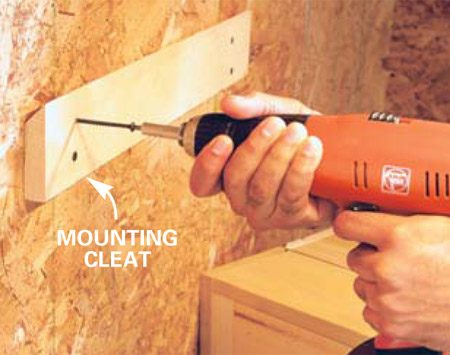 <b>Photo 5: Hang the box on a cleat</b></br> Position the other half of the mounting cleat about 40 in. above the work surface and fasten it to the wall studs with four 3-in. screws. Hang the cabinet and drive two 3-in. screws through the bottom 1x 2 into the wall studs for extra strength.