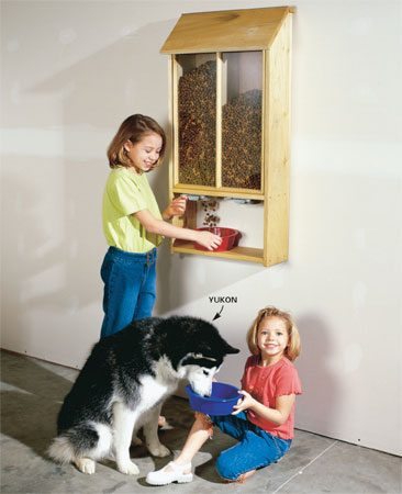 "<b>Pet food dispenser in action</b></br> Slide open the ""blast gate"" and food falls into the dish. A hinged top allows easy refilling."