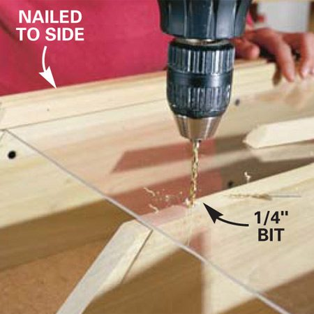 <b>Photo 7: Enlarge the acrylic screw holes</b></br> Remove the center molding and enlarge the hole in the acrylic with a 1/4-in. bit to provide room for expansion. Press the drill gently so the bit doesn't grab and crack the acrylic. Replace the molding and nail it on. Cut the piano hinge to length and screw it to the top.