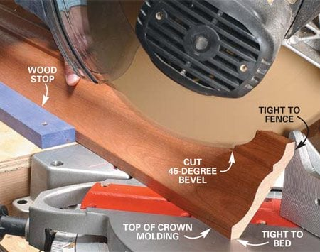 <b>Photo 9: Cutting the bevel in crown molding</b></br> Position your crown molding upside down in the miter box at the angle it will rest on the wall (flat spots tight to the bed and fence). Screw or clamp a stop to the extension table to support the crown molding at the correct angle.
