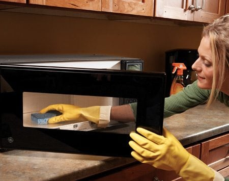 <b>Heat sponge in the microwave first</b></br> Grease and dirt build up on kitchen cabinets over time. To clean your cabinets, first heat a slightly damp sponge or cloth in the microwave for 20 to 30 seconds until it's hot. Put on a pair of rubber gloves, spray the cabinets with an all-purpose cleaner containing orange oil ($4), then wipe off the cleaner with the hot sponge.