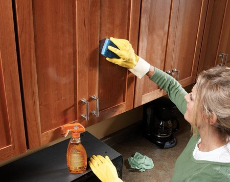 <b>Wipe cabinets with all purpose cleaner</b><br/>For stubborn spots, let the cleaner sit for five minutes first. Wipe in the direction of the wood grain. Rinse and reheat the sponge as it becomes saturated. Then wipe the cabinets with a cool, damp cloth. The orange oil leaves a shiny coating. This works for any wood or metal surface.