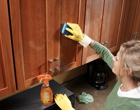 <b>Wipe cabinets with all purpose cleaner</b></br> For stubborn spots, let the cleaner sit for five minutes first. Wipe in the direction of the wood grain. Rinse and reheat the sponge as it becomes saturated. Then wipe the cabinets with a cool, damp cloth. The orange oil leaves a shiny coating. This works for any wood or metal surface.