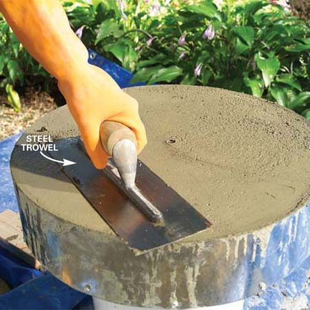 <b>Photo 9: Smooth the concrete</b></br> Smooth the soupy layer of cement with a steel trowel. Let the concrete harden overnight.