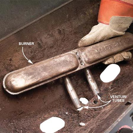 <b>Photo 7: Remove the burner</b></br> <p>Pull out the burner, sliding the venturi tubes free from their mounting slots. If the burner has heavy rust or is rusted through, replace it.</p>