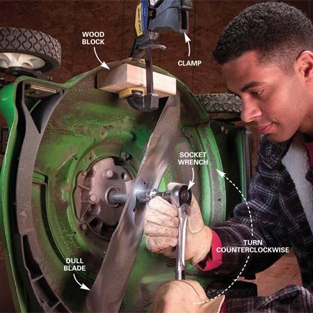 <b>Photo 12: Remove the cutting blade</b></br> Disconnect the spark plug wire, turn off the fuel valve and seal the gas tank (Photo 2). Then clamp a block of wood to the lawn mower deck with the sharp edge of the blade against the block. Remove the blade by turning the large nut counterclockwise with a socket wrench.