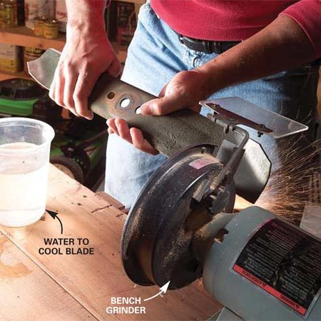 <b>Photo 13: Sharpen the cutting blade with a grinder</b></br> Sharpen blades with nicks or rounded cutting edges on a grinder. Hold the blade firmly and tilt it so the grinding wheel contacts it at the original angle (about a 30-degree bevel). Move the blade steadily across the grinding wheel while applying slight pressure. Dip it in water after each pass to cool it.