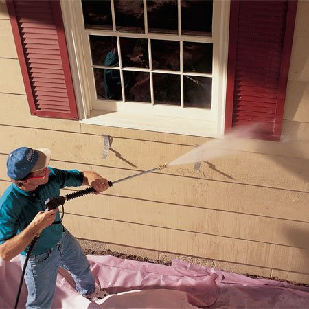 <b>Photo 1: Pressure wash to remove dirt</b></br> Pressure washing removes loose paint and built-up grime and improves paint adhesion. Use the high pressure carefully, especially around windows. High-pressure water can break the glass. Avoid directing water up under the laps, and keep the nozzle at least 16 in. away from the wood.