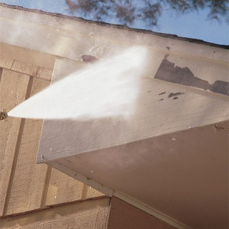 <b>Photo 2: Pressure wash to remove paint</b></br> Some loose paint will flake off while you wash the surface. But don't try to strip the paint—you'll gouge the wood.