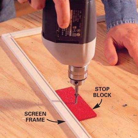 <b>Photo 2: Secure the frame</b></br> Place wooden blocks along the inside of the two longest sides of the frame and secure them to the work surface. The blocks keep the frame from bowing inward when you install the new screen material.
