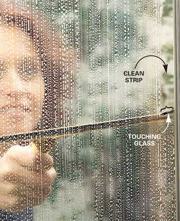 <b>Photo 3: Clean a starting strip</b></br> Tip the squeegee so that only the corner contacts the glass. Then, starting at the top corner of the glass, clean a narrow strip of glass from top to bottom on one side. This clean strip makes it easier to start the horizontal stokes.
