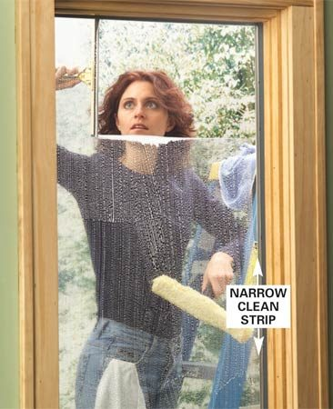 <b>Photo 4: Squeege across the top</b></br> Press the squeegee blade against the glass in the upper corner and pull it steadily across the window. Concentrate on keeping the top of the squeegee in contact with the top edge of the window.
