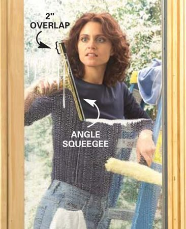 <b>Photo 6: Work down the window</b></br> Begin again, with the top of the squeegee overlapping the previous stroke about 2 in. Pull the squeegee across the window at an angle to direct excess water down. Wipe and repeat.