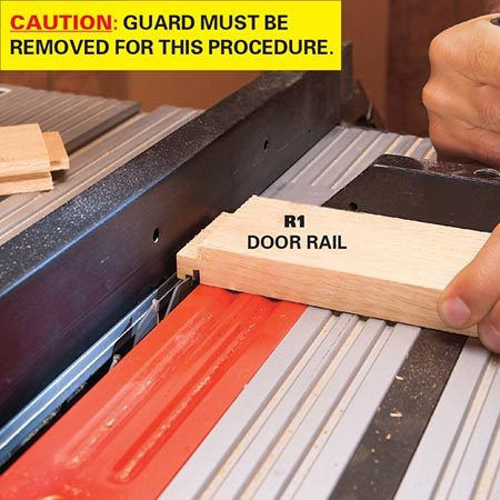 <b>Photo 12: Cut the tenons</b></br> <p>Cut tenons on each end of the door rails using your table saw fence as a guide. The tongues should be 1/2 in. long and must fit snugly into the grooves of the stiles. Cut a test piece first to get the right setting.</p>