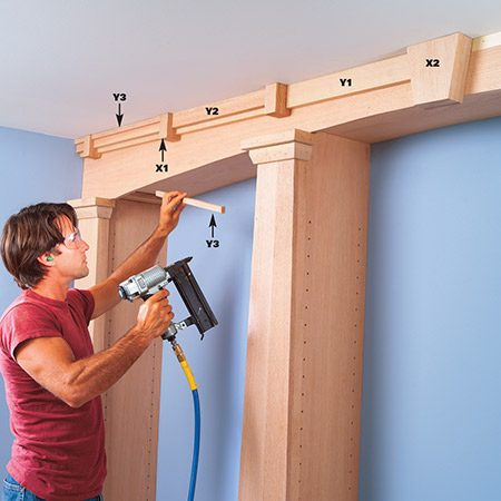 <b>Photo 20: Construct the cornice assembly</b></br> <p>Cut cornice blocks from 3/4-in. oak, then stack them in layers and glue them to achieve the 2-1/4 in. thickness. Make the tapered keystone center block in the same manner. Predrill, glue and hand-nail the cornice blocks to the curved apron with 10d finish nails. Next cut the cornice strips on the table saw and nail them in layers between the blocks with your finish nailer.</p>