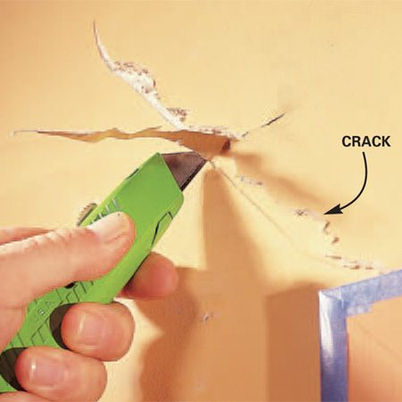 <b>Photo 1: Cut</b></br> Cut a V-notch through the full length of the crack, 1/8 to 1/4 in. deep, removing all loose wall material.  Protect woodwork with masking tape.