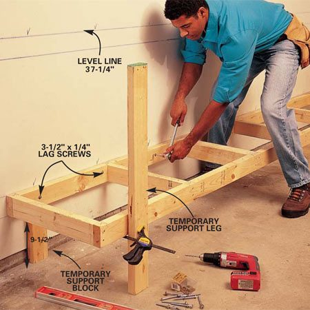 <b>Photo 2: Install the lower shelf</b></br> Snap two level lines at 37-1/4 in. (bench frame height) and 13 in. (shelf frame height) from the floor the length of the bench. (Note: Garage floors often slope toward the door, but the ceiling or top framing is level.) Begin your layout on the wall on the end of the bench that's farthest from the door. Rest the shelf framing sections on the temporary support blocks, and clamp temporary 4-ft. legs to the front of the framing, holding the shelf level. Bolt the rear 2x4 to every wall stud with a 3-1/2 in. x 1/4-in. lag screw.