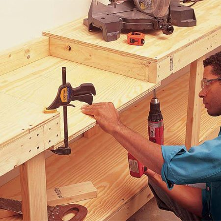 <b>Photo 4: Form the miter saw bay</b><br/>Cut out the 2x4 rail in the front of the open miter saw bay with a handsaw. Fasten the 3/4-in. plywood miter saw shelf to the underside of the 2x4s in the miter saw bay with 3-in. screws at each side and into the rear rail. Screw a 2x4 support to the backside of the legs on either side of the miter saw bay to support the shelf (Fig. A).