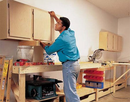 <b>Photo 15: Hang cabinets</b></br> 15 Fasten 12-in. deep wall cabinets to wall studs with 3-in. screws.