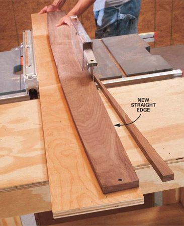 <b>Photo 8: Push the plywood through</b></br> Set the fence to remove the least amount of material and trim the attached board. Using the standard ripping procedure shown in Photo 2, guide the edge of the plywood against the fence as you run the board and plywood through the saw blade. Unscrew the board from the plywood and rip it again with the newly created straight edge against the fence.