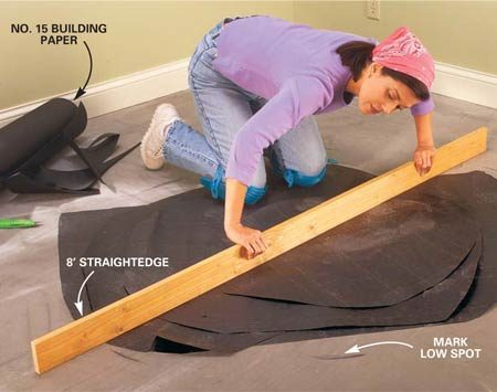<b>Photo 2: Check for low spots in the floor, then fill them in.</b></br> Check for low spots in the floor with an 8-ft. straightedge and mark their perimeter with a pencil. Fill depressions less than 1/4 in. deep with layers of building paper. Fill deeper depressions with a hardening type floor filler available from flooring stores.