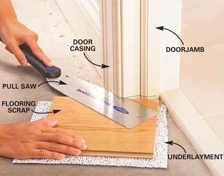 <b>Photo 3: Use a pull saw to cut the doorjambs and casings</b></br> Undercut doorjambs and casings (door moldings) to make space for the flooring to slip underneath. Guide the saw with a scrap of flooring stacked on a piece of underlayment.