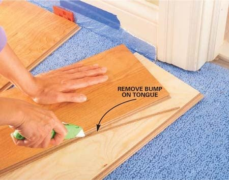 <b>Photo 9: Prep flooring to fit around doorjambs</b></br> Plan ahead when you get near a doorjamb. Usually you have to slide the next piece of flooring under the jamb rather than tilt and snap it into place. To accomplish this, you must slice off the locking section of the tongue from the preceding row with a sharp utility knife before installing it.