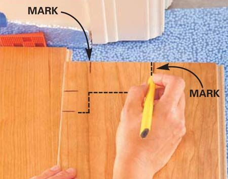<b>Photo 11: Finish marking the plank for cutting</b></br> Align the flooring lengthwise and mark for the notches in the other direction, allowing for the floor to slide under the doorjamb about 3/8 in. Connect the marks with a square and cut out the notch with a jigsaw.