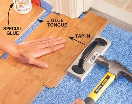 <b>Photo 12: Glue and install the notched piece</b></br> Apply a thin bead of the manufacturer's recommended glue along the edge where the portion of the tongue was removed. Slide the notched piece of flooring into place and tighten the glued edge by pounding on the special tapping block.