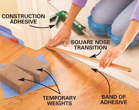 <b>Photo 13: Install the transition strip</b></br> Cut a transition molding, in this case a square nose transition, to fit between the doorstops or jambs. Spread a bead of construction adhesive only on the area of the concrete floor that will be in contact with the transition piece. Set the transition in place and weight it down overnight.