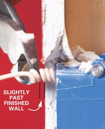 <b>Photo 3: Snip to size</b></br> Press the coiled end tight to the outlet-mounting screw hole. Snip the coil so it extends just past the wall; the insulation will compress slightly when tightened.