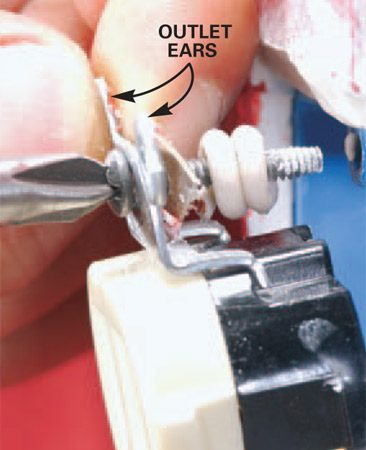 <b>Photo 4: Tighten down</b></br> Slide the coil spacer over the outlet-mounting screw. Screw the outlet down until the outlet ears are flush to the wall.