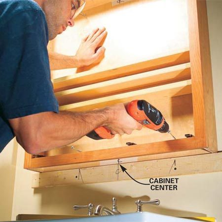 <b>Photo 3: Install the cabinet</b><br/>Set the cabinet on the ledger and line up the center of the cabinet with the center mark on the ledger. Drive the screws into the studs, then remove the ledger. Fill the screw holes with spackling compound and touch up the paint.